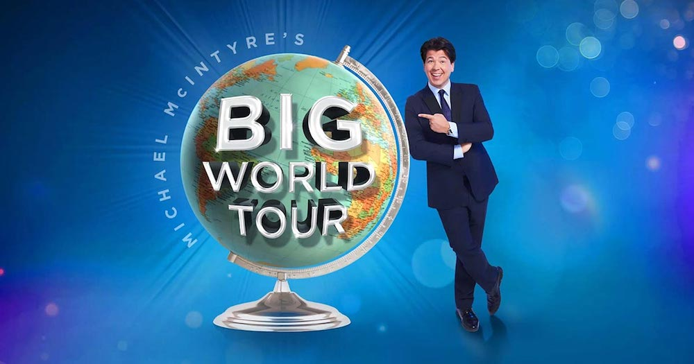 man against blue backdrop leaning against large world globe