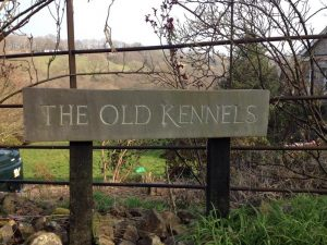the old kennels sign against trees