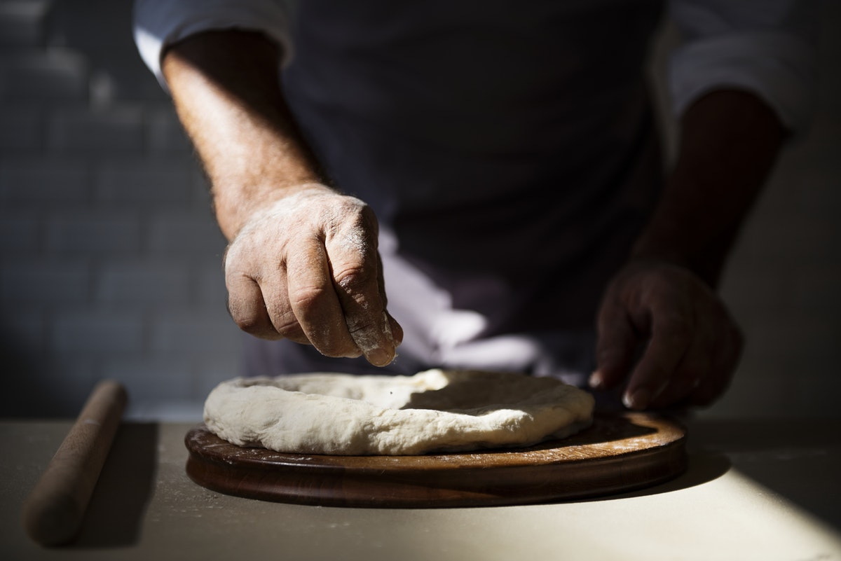 man baking dough bread board