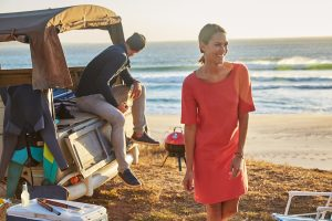 woman in red dress on beach with man sat on the back of a van
