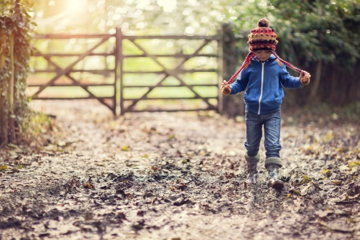 boy walking in mud gate woolly hat