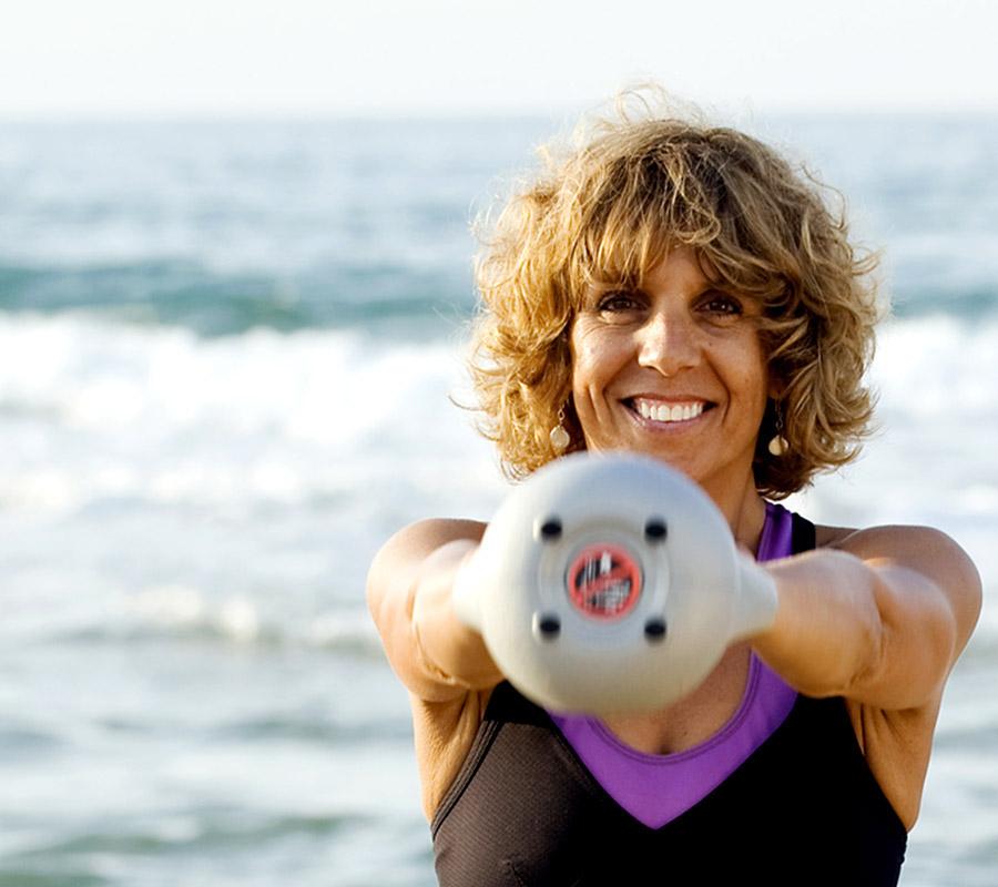 woman with curly hair holding kettle ball with sea in background