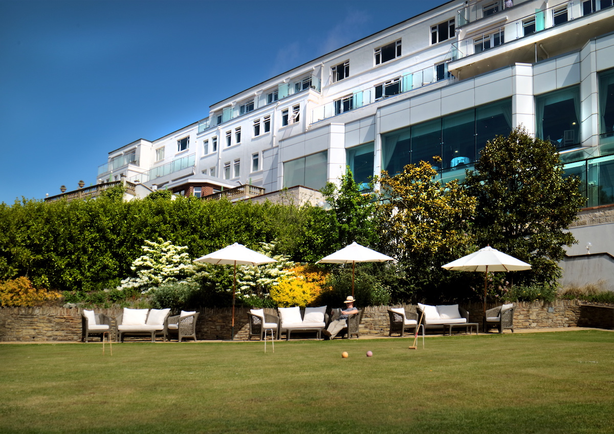 exterior white hotel with green and outdoor seating