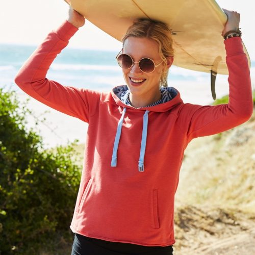 woman in red hoodie on beach holding surfboard