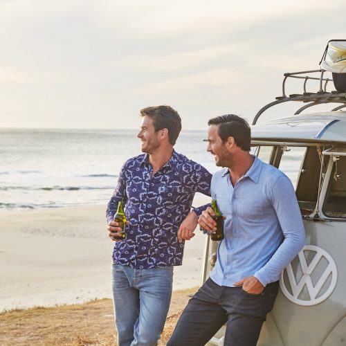 men leaning against VW camper van on beach