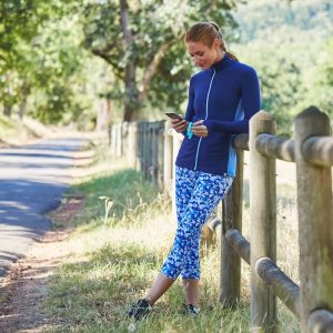 woman in blue leggings and base layer leaning against a fence in countryside