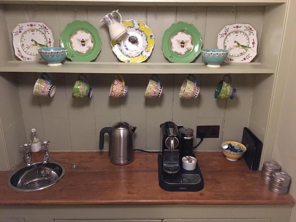 dresser with coffee machine and plates and mugs