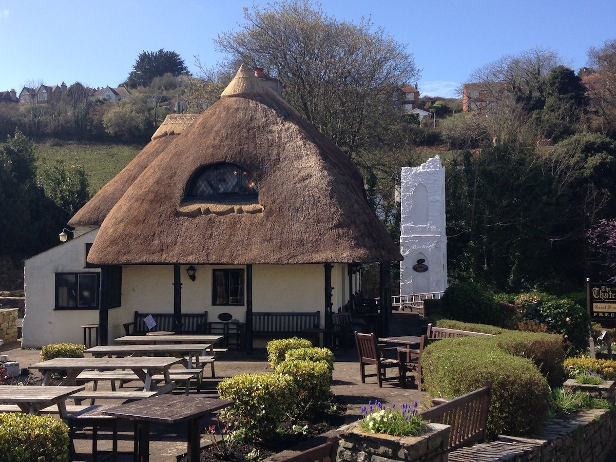 Thatched roof pub with picnic benches blue skies