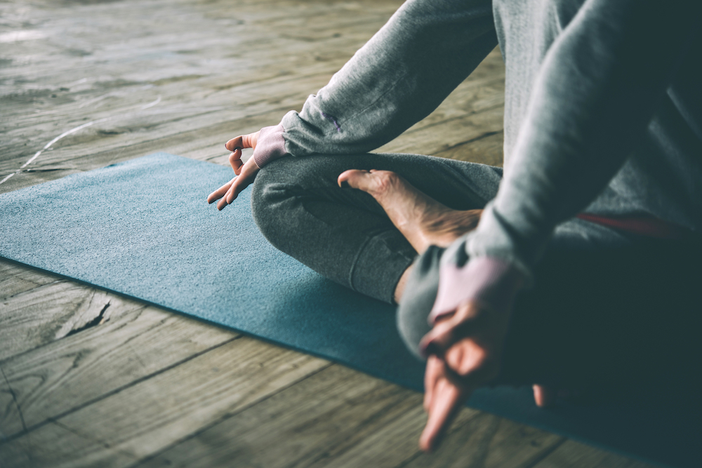 Yoga pose on a mat on wooden floor