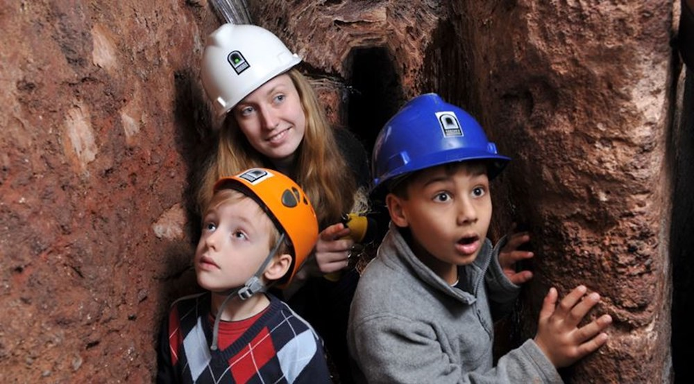 family underground wearing hard hats