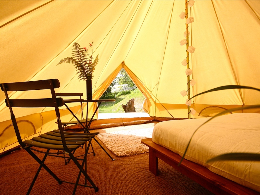 interior bell tent with seagrass floor double bed table and chairs