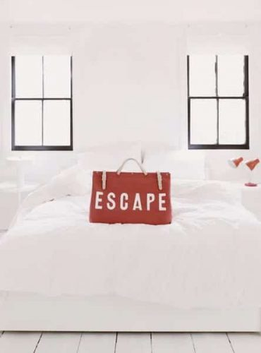 red bag with escape written on it on white bed with windows