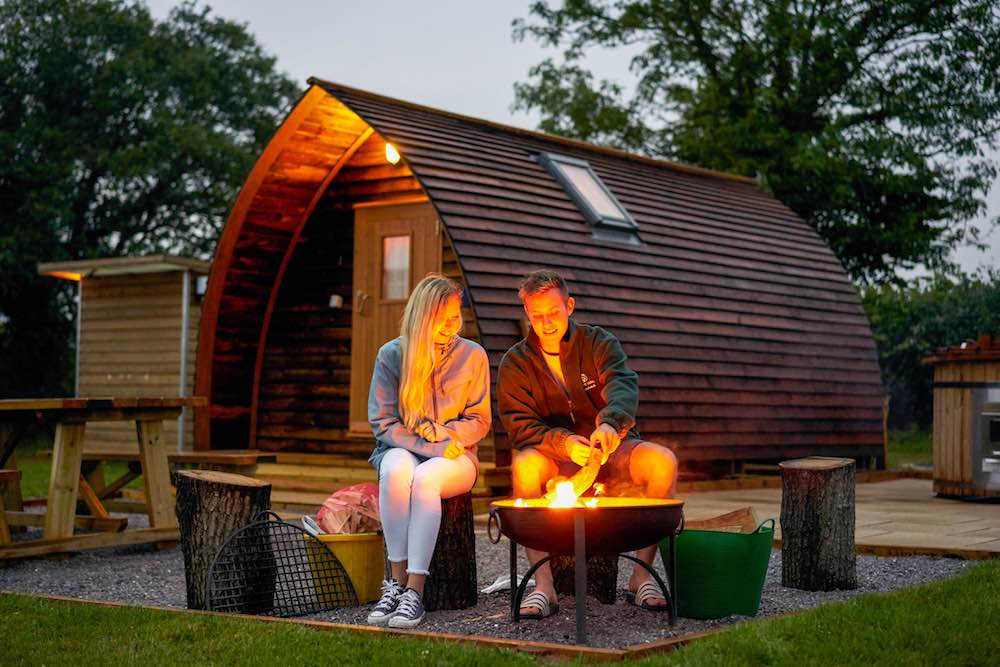 couple sat outside wigwam