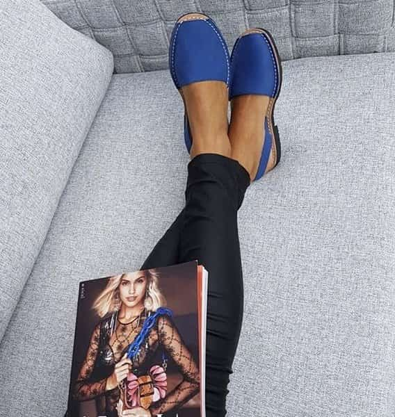 blue sandals on woman in black leggings and magazine on lap