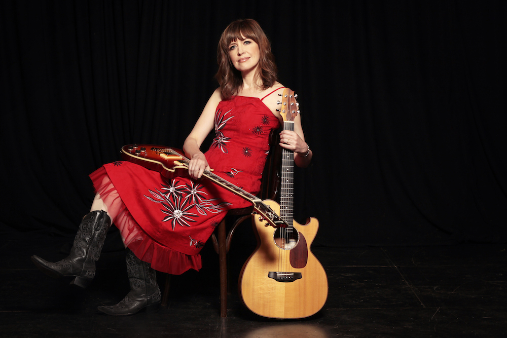woman in red dress with guitars on black background