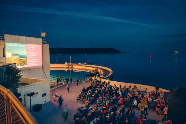 outdoor swimming pool by the sea with cinema screen