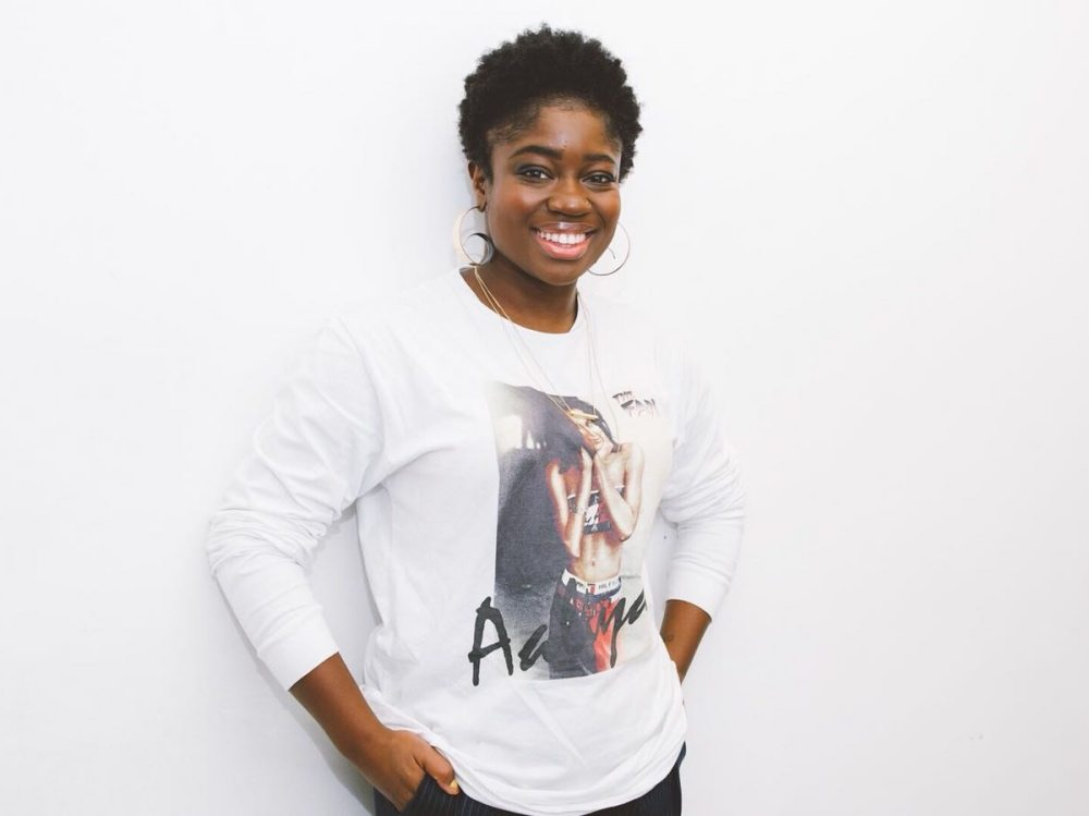 black woman in white jumper against black background