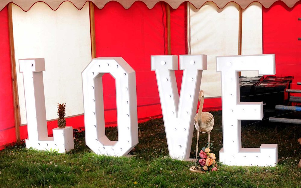 red and white marquee with big white letters spelling love on grass