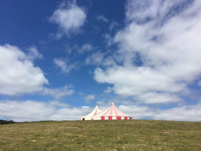 red and white big top tent in field against blue sky
