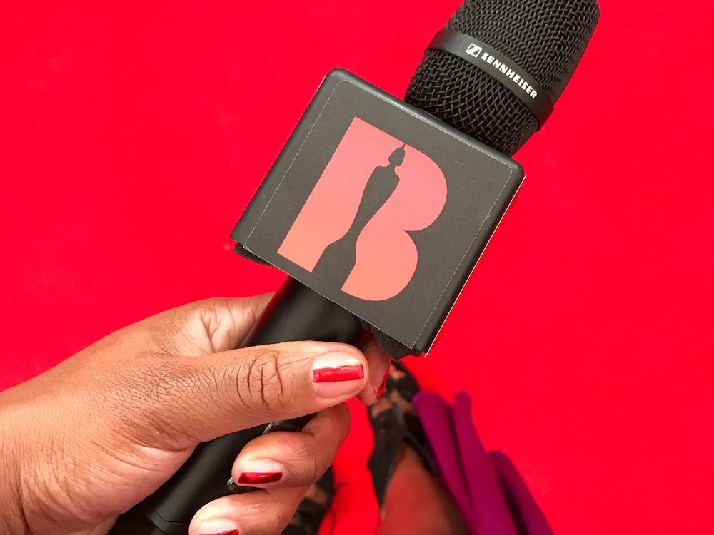 woman holding microphone against red background