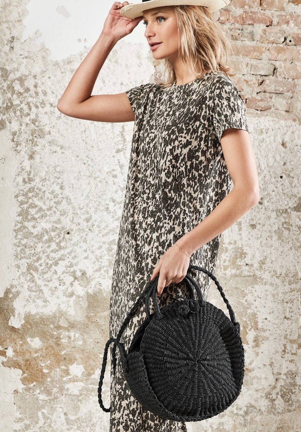 woman in print dress with black bag