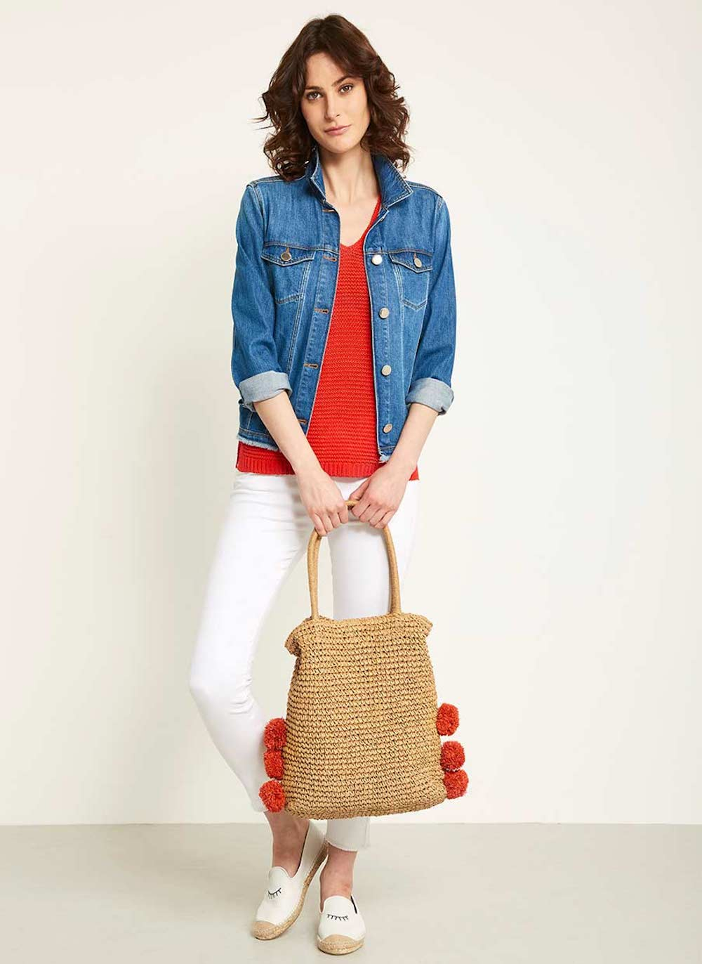 woman in white jeans denim shirt red top and tan bag