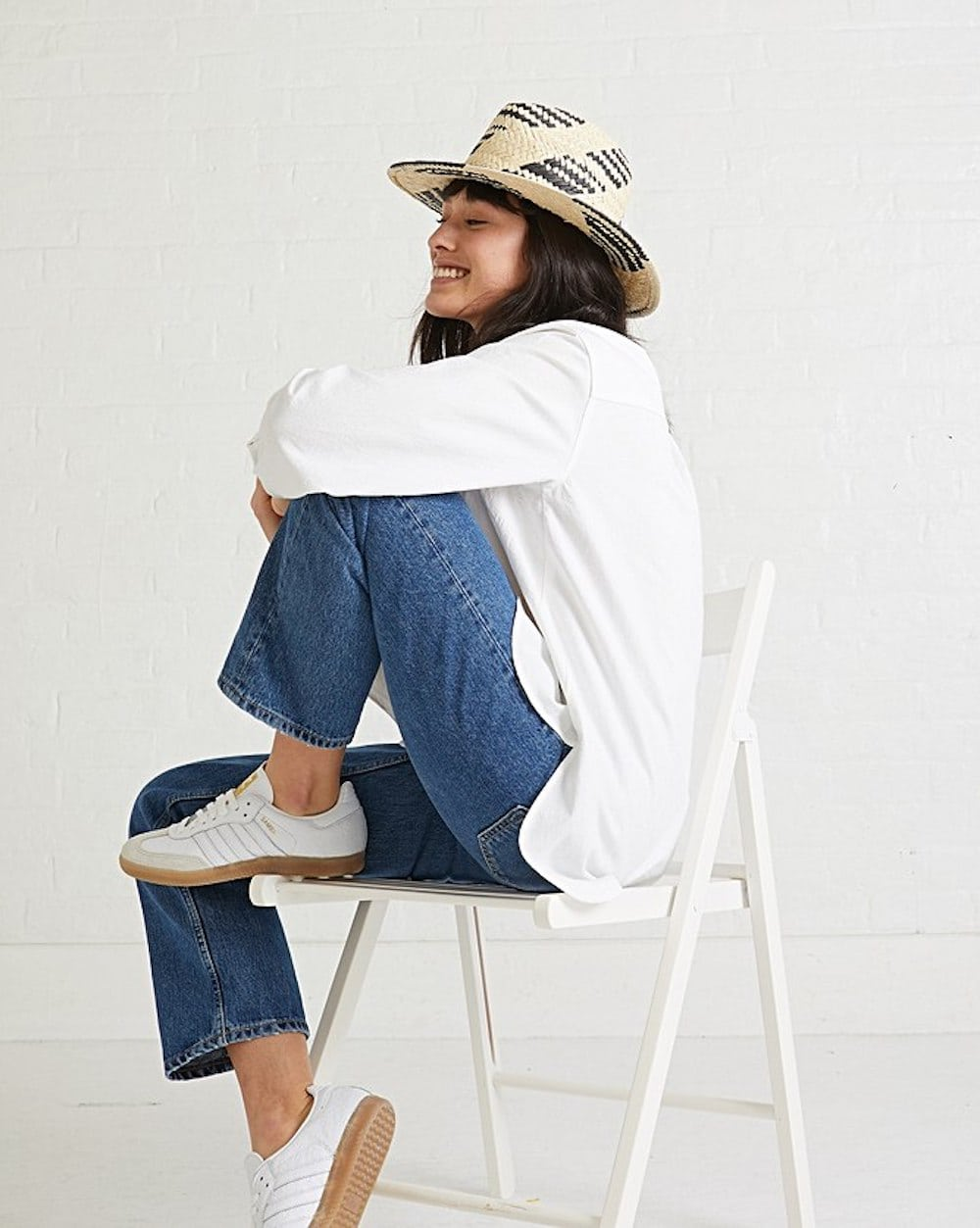 woman sat on chair with jeans and white shirt and straw hat