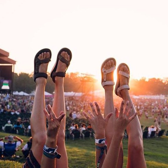 feet wearing sandals in the air at festival
