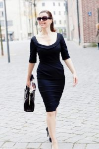 woman walking in black dress and sunglasses
