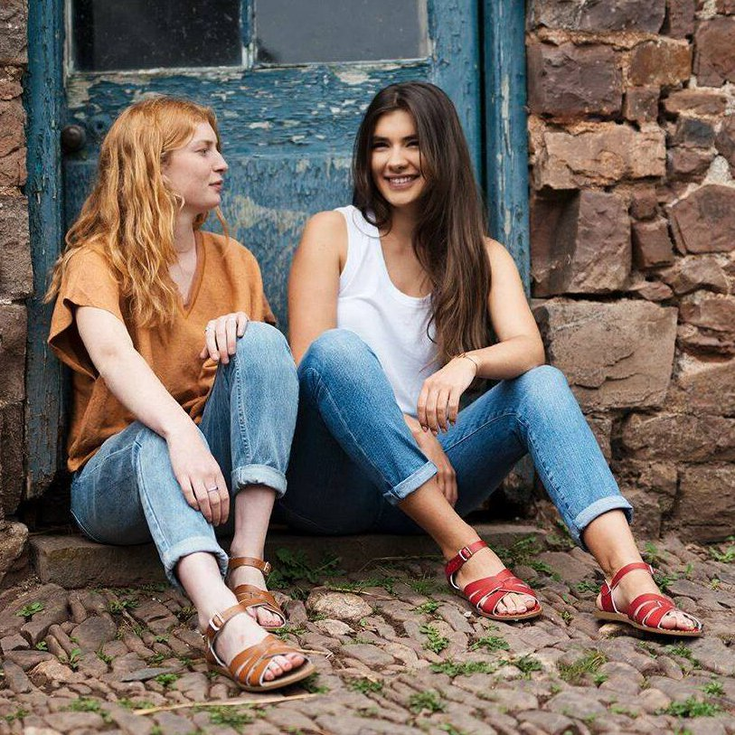 two women sat wearing jeans and sandals
