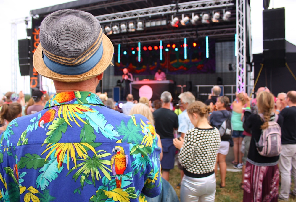 man in tropical print shirt and hat at festival