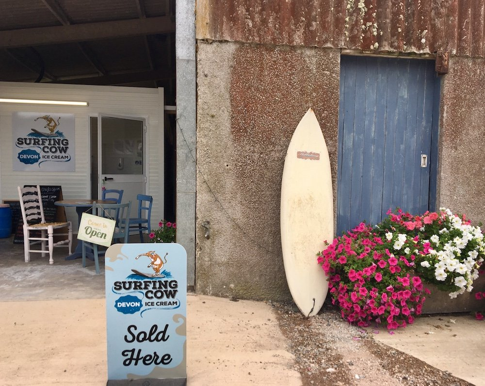 surfboard sign flowers blue door