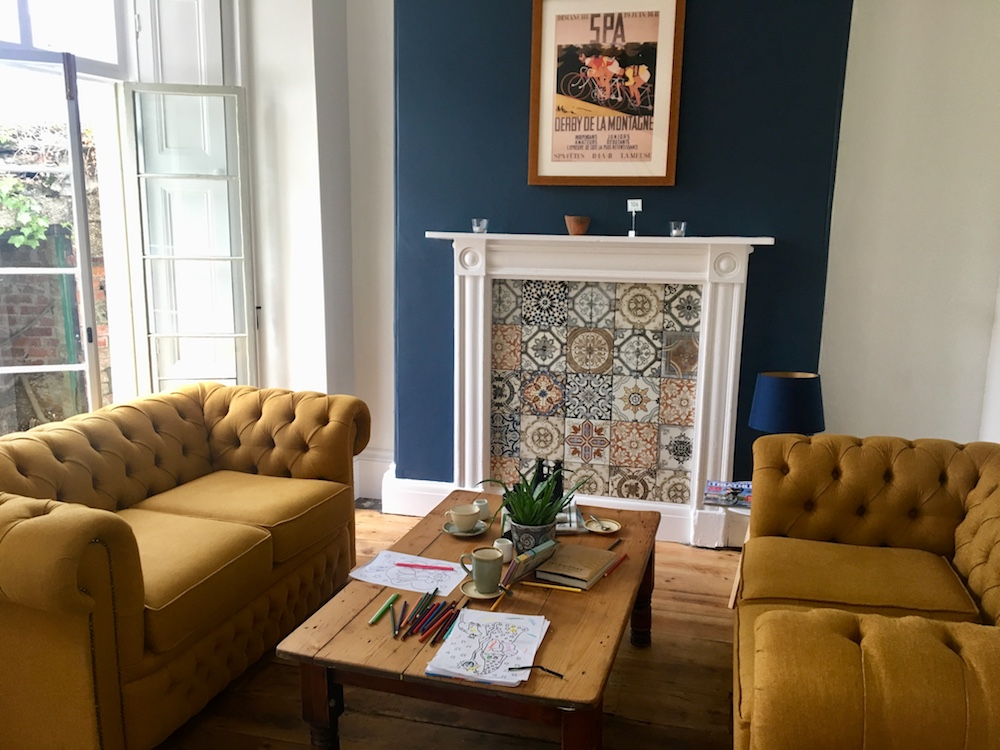 mustard sofas blue wall tiled fireplace