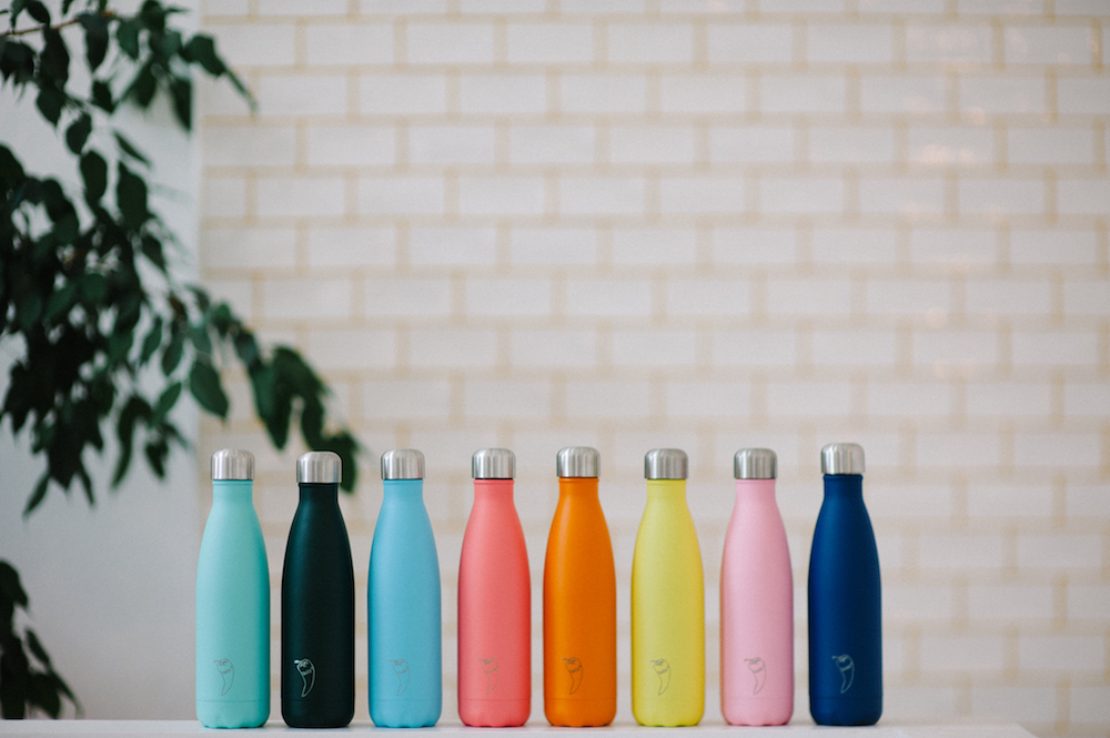 colourful water bottles against white tiled wall