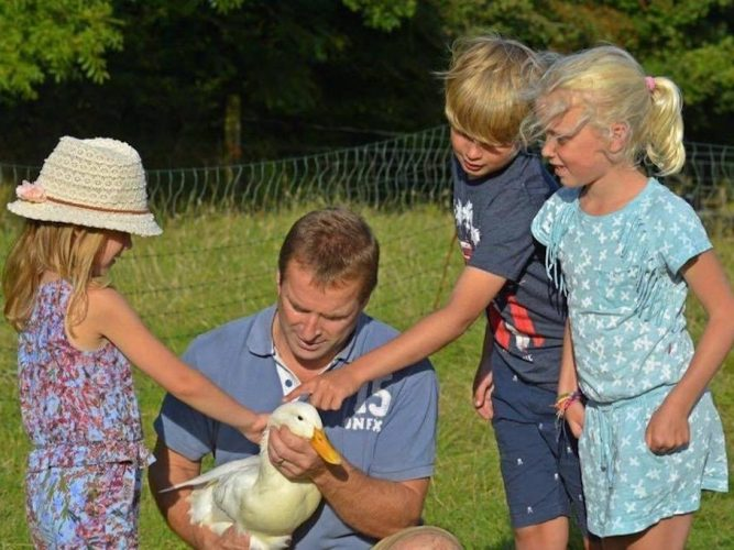 man holding duck with children