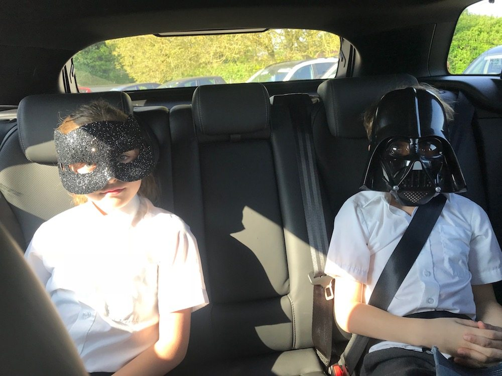 children in back seat of car wearing masks
