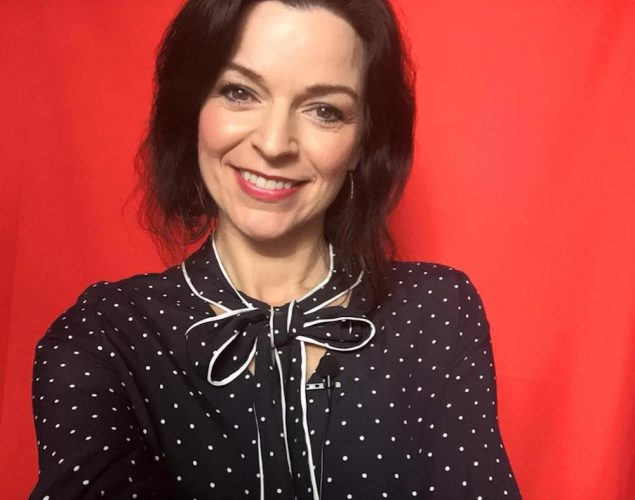 woman in black polka dot blouse against red wall