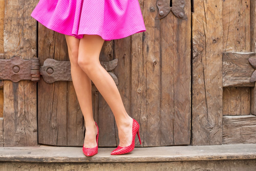 woman in pink skirt and pink stilettos against wooden fence