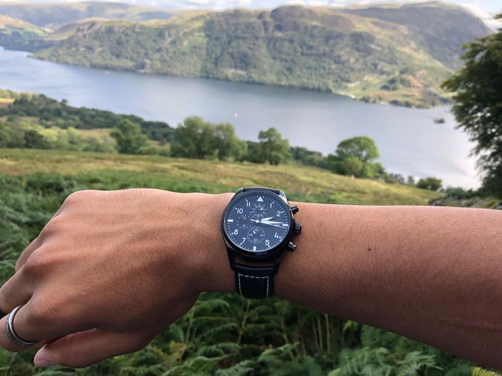 watch on wrist with lake and countryside