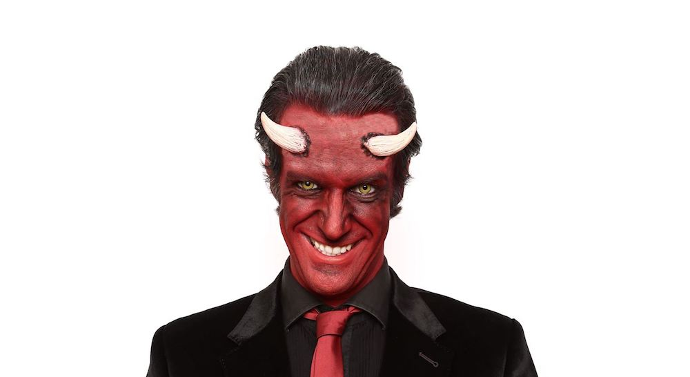man in make up with horns and black suit red tie