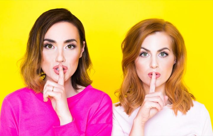 women with finger to lips against yellow wall
