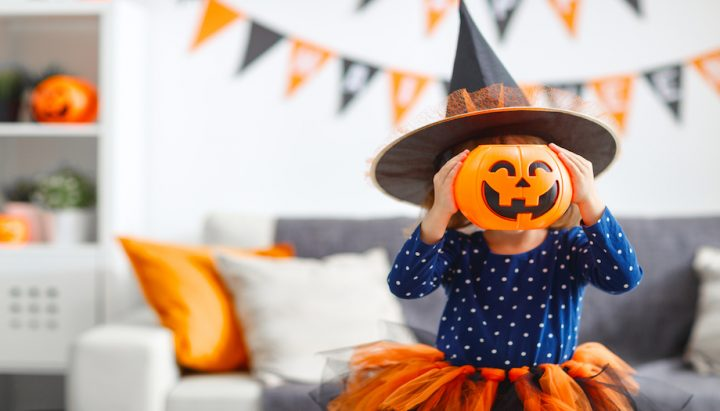 girl in witches hat with pumpkin