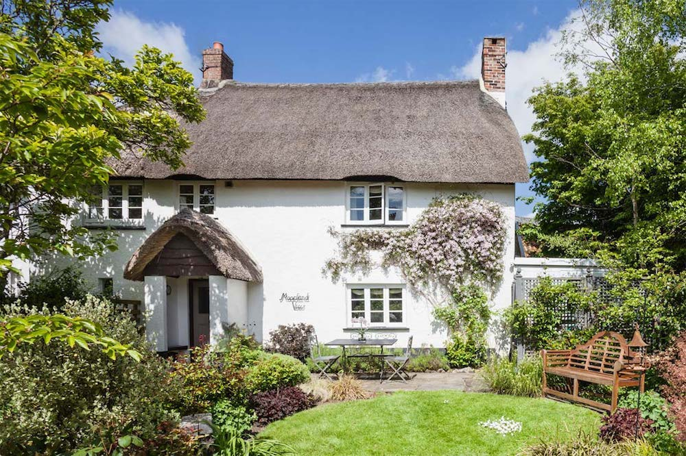 exterior thatched cottage blue sky